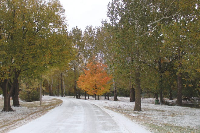 Brilliant fall foliage is accented by the first white snowfall of the season Monday at Pratt's Lemon Park. Slick roadways and icy paths were the result of an arctic blast that settled over much of Kansas on October 26, leaving a mixture of snow, ice and rain in its wake.
