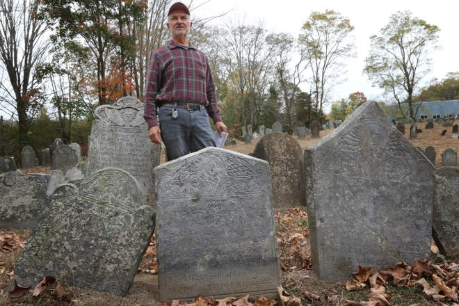 Historian David Oat stands in the Old Norwichtown Burial Ground where the footstone of Diadema Carew, 3, and her sister Lucretia Carew, 10 months, two little girls who died of diphtheria in 1732, belongs. Hopkinton couple, Allison Palombo and Christopher Mongeau, found a grave marker inside their tree. The footstone of the grave was stolen after 1933. [The Providence Journal / Sandor Bodo]
