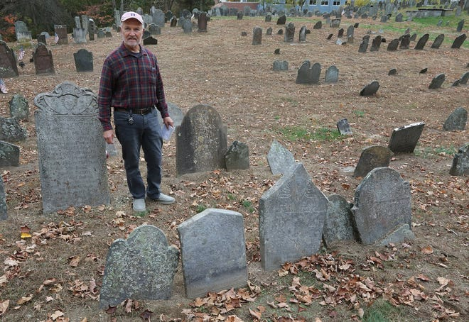 Historian David Oat marks the spot in the Old Norwichtown Burial Ground where the footstone of Diadema Carew, 3, and her sister Lucretia Carew, 10 months, stood before it was taken. It ended up nearly sealed in a tree in Hopkinton, RI.  The two little girls died of diphtheria in 1736. [The Providence Journal / Sandor Bodo]