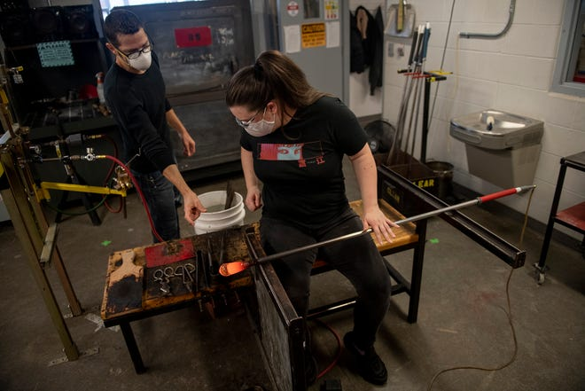 Kent State glass blowing artists are using a new apparatus so that they don't have to use their breath or take off their masks to create their art. Glass department head Davin Ebanks interacts with Sarah Ferraro, an art history major with a glass minor, as she works on a piece using a pedal to control the amount of air going in the pipe from a rubber tube.