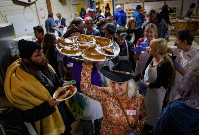 Volunteer Janie Gunnell maneuvers a platter of pie through the crowded dining hall at the 30th annual Whiteaker free community Thanksgiving dinner.