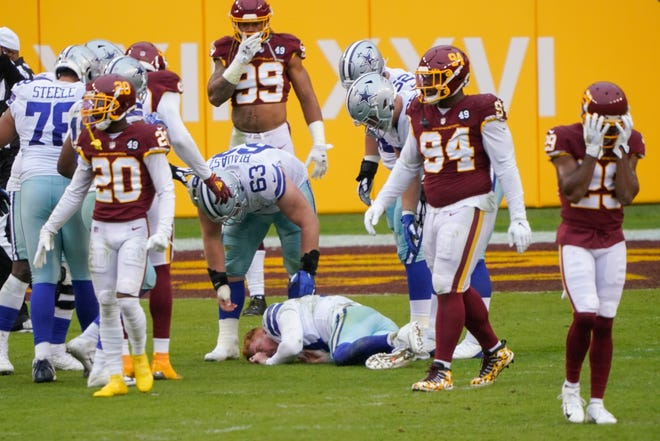 Players reacting to seeing Dallas Cowboys quarterback Andy Dalton (14) lying on the ground after getting hit by Washington Football Team inside linebacker Jon Bostic (53) in the second half on  Sunday in Landover, Md.