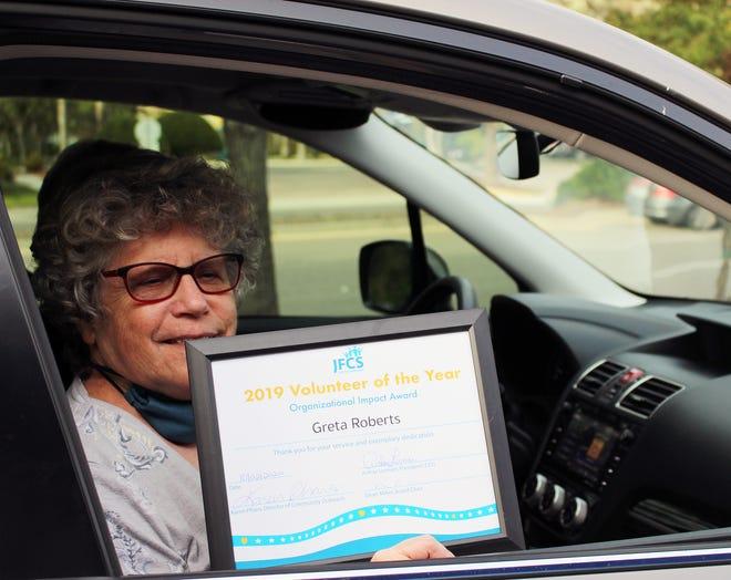 Award winning JFCS volunteer Greta Roberts picks up her certificate and pizza.