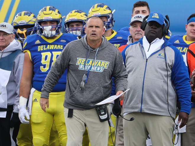 At a 2019 game, Delaware head coach Danny Rocco, assistant coaches and players watch from the sidelines at Delaware Stadium.