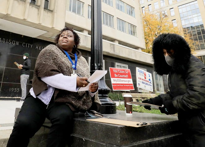 Theola Carter, left, and Carrie Braxton fill out their ballots on the first day of the state's in-person absentee voting window for the Nov. 3 election outside the City-County Building Oct. 20 In Madison, Wis.