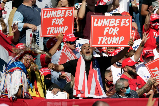 "Supporters hold ""Lumbees for Trump"" signs as President Donald Trump speaks during a campaign rally at the Robeson County Fairgrounds in Lumberton, N.C., Saturday, Oct. 24, 2020. (AP Photo/Chris Seward)"