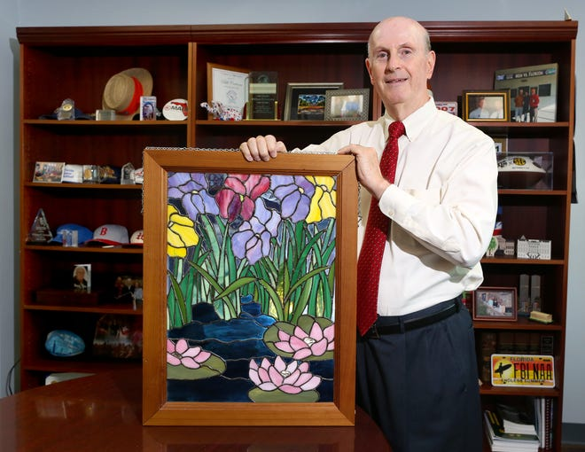 Bill Cervone, the retiring State Attorney for the 8th Judicial Circuit, holds up a stained glass window he made, at his office in Gainesville.