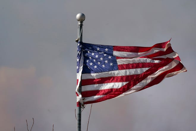 The American flag is blown by heavy winds as smoke rises from mountain ridges as a wildfire burns Oct. 22 near Granby, Colorado.