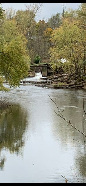 Water in the Stillwater Creek is flowing through the side as the River Reach Construction crews prepare for demolition of the lowhead dam in Uhrichsville.