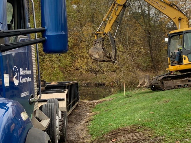 A crew from River Reach Construction, of Barberton, cleans up around the Stillwater Creek in Uhrichsville. The trees were cut in the spring for the project that will result in the demolition of the lowhead dam. Cleanup is expected to last through the week with demolition expected to begin Monday or Tuesday.