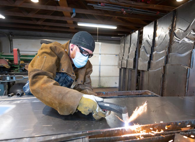 Eric McCue uses a plasma cutter to slice through steel panels Monday. McCue is using the panels to create the sculpture on the right that will be honoring first responders.