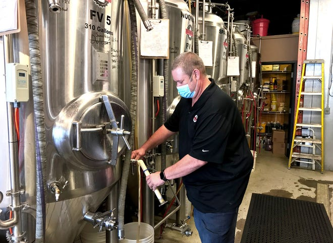 Frank Barickman checks the progress of brewing underway at Restoration Brew Worx, 25 N. Sandusky St. in Delaware. Barickman was one of several local merchants who on Oct. 21 told Delaware City Council that Ohio's 10 p.m. closing for liquor sales is causing financial losses for the businesses.