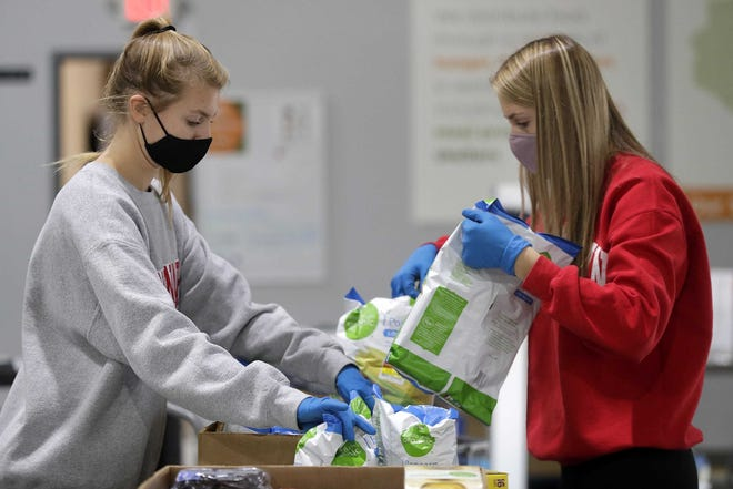 Volunteers Bre, left, and Madison Lortscher box donated food at Feeding America Eastern Wisconsin in Little Chute.