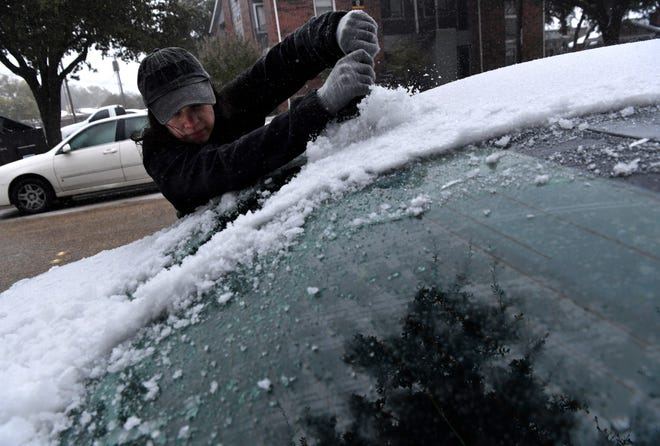 Ariel McBratney clears ice from her car Tuesday near The Landing apartment on Texas Avenue. While most people stayed indoors during the winter storm, McBratney had to venture onto Abilene's icy streets for her son's doctor's appointment.