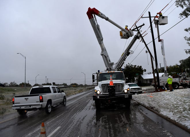 A motorist passes a crew from American Electric Power replacing a utility pole at South Fifth Street and Danville Drive after a pickup slid into it earlier that morning. Icy roads became slicker as the day progressed, causing numerous accidents around Abilene.
