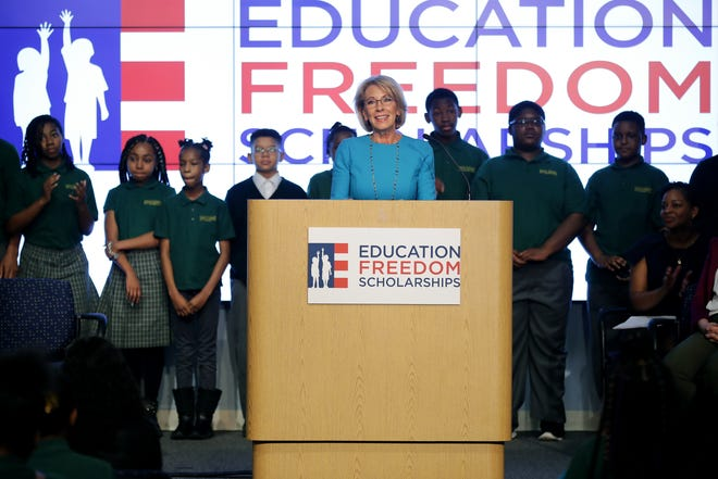 """U.S. Education Secretary Betsy DeVos stands in front of students from Digital Pioneers Academy during an event to discuss her proposal for Education Freedom Scholarships at the Education Department headquarters February 28, 2019 in Washington, DC.  According to the department, the scholarships will be funded with $5 billion of federal tax credit for donations to scholarships for private schools and other educational programs and would """"significantly expand education freedom for millions of students and families across the country."""""""