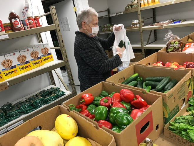 Volunteer Agatha Paul -- who also is a client -- packages produce for food boxes provided to families in need by the Kewaunee County Food Pantry in Algoma.