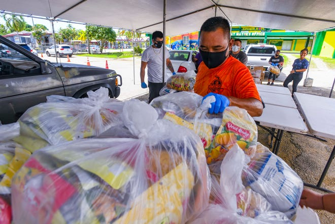 The Agat Mayor's Office gives out food commodities residents during a drive-through distribution in this Oct. 27 file photo. The Guam Department of Education is continuing the distribution of food commodities through village mayors Nov. 16-20.