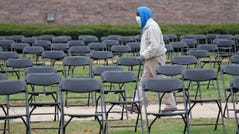 Johnnie Hodges, of Milwaukee, on his way to register to vote, walks through an isle of empty chairs at the newly created Milwaukee COVID-19 Memorial at MacArthur Square in Milwaukee on Tuesday. The memorial consists of nearly 600 empty chairs to represent lives lost due to the Covid-19 pandemic.