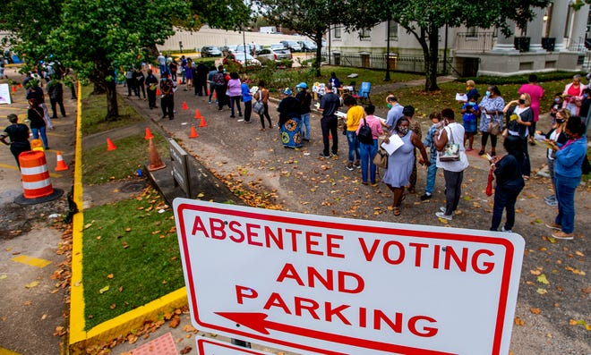 A line of voters loops through the parking lot of the Montgomery County Courthouse as they wait to vote absentee in Montgomery, Ala., on Tuesday morning October 27, 2020.