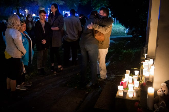 People gather during a vigil outside of the home where 14-year-old Sayeed Neilson was found dead last week in the Hermitage neighborhood of Nashville, Tenn., Monday, Oct. 26, 2020. The mother and brother of the teen, Rebecca Greenwood, 52, and David Matheny, 33, were arrested Saturday morning on charges of criminal homicide after the teen was found dead from assault-related trauma.