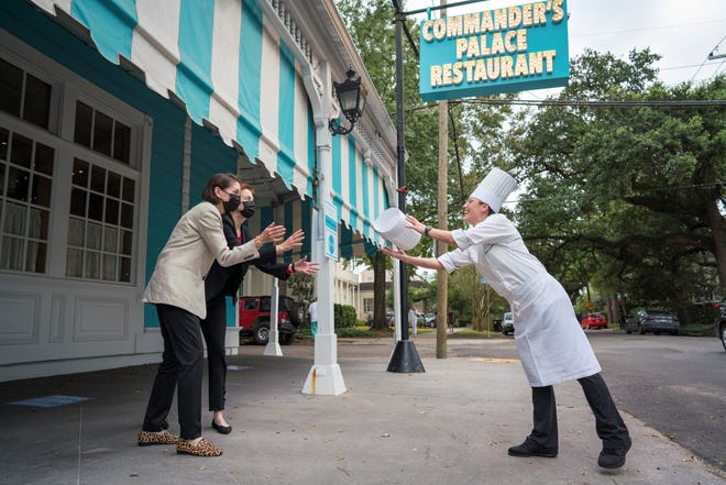 Lally Brennan (left front) and Ti Martin (left rear), proprietors of Commander's Palace in New Orlean, toss a chef's toque to Meg Bickford, the restaurant's new executive chef. (Courtesy Commander's Palace)