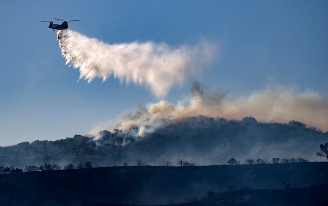 A helicopter drops retardant on the Silverado wildfire off Santiago Canyon Road where fierce winds have caused problems on Monday, Oct. 26, 2020, in Irvine, Calif.