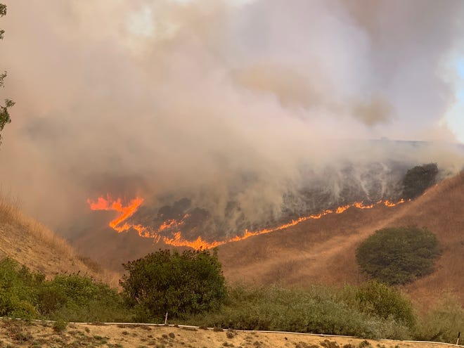 Flames from the Blue Ridge Fire can be seen on a ridge above Yorba Linda, Calif., on Oct. 26, 2020.