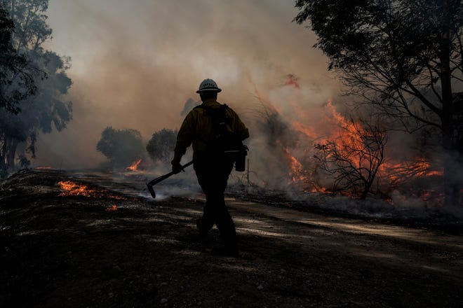 A firefighter prepares to put out hotspots while battling the Silverado Fire, Monday, Oct. 26, 2020, in Irvine, Calif. The fast-moving wildfire forced evacuation orders for 60,000 people in Southern California on Monday as powerful winds across the state prompted power to be cut to hundreds of thousands to prevent utility equipment from sparking new blazes.