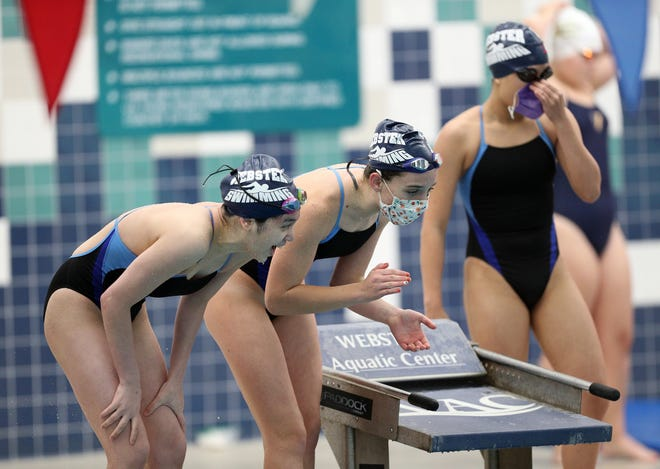Webster's Vivian Nguyen, Marin Bedford and Nakisha Dinh, cheer on teammate Meaghan Martin in the 200 medley relay during a regular season meet at Webster Aquatic Center in fall 2020.