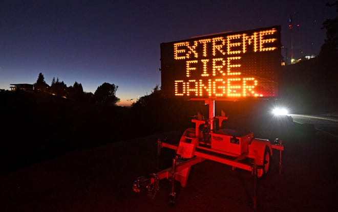 A roadside warns motorists of extreme fire danger on Grizzly Peak Blvd. in Oakland on Sunday, Oct. 25, 2020. Due to high winds and dry conditions PG&E turned off power to over 361,000 customers in 36 counties to protect them from possible wildfires caused by downed power lines.
