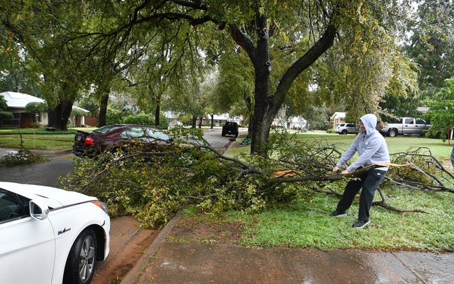 Matthew Meyer drags a broken tree limb out of the street as shown in this Oct. 27, 2020, file photo. Ice accumulation on trees caused downed limbs across the area in the October storm. The latest winter storms wreaked havoc on water pipes and caused other damage.