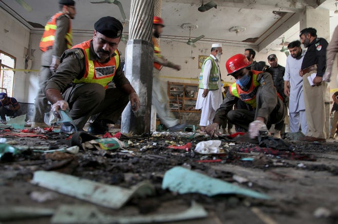 Pakistani rescue workers and police officers examine the site of a bomb explosion in an Islamic seminary, in Peshawar, Pakistan, Tuesday, Oct. 27, 2020.