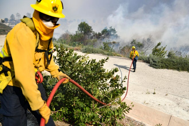 Los Angeles County Firefighters contain The Silverado Fire in Irvine, Calif. on Oct. 26, 2020.