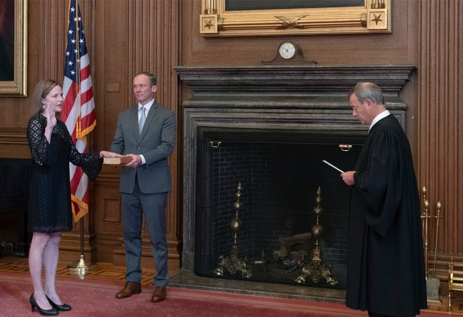 Chief Justice John G. Roberts, Jr., administers the Judicial Oath to Judge Amy Coney Barrett in the East Conference Room, Supreme Court Building. Judge Barrett's husband, Jesse M. Barrett, holds the Bible.
