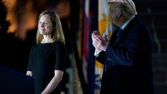 President Donald Trump looks toward Amy Coney Barrett, before Supreme Court Justice Clarence Thomas administers the Constitutional Oath to her on the South Lawn of the White House in Washington, Monday, Oct. 26, 2020, after Barrett was confirmed by the Senate earlier in the evening.