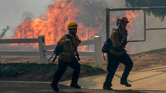 Firefighters react to approaching flames at the Blue Ridge Fire on Oct. 27, 2020 in Yorba Linda, California. Strong Santa Ana Winds gusting to more than 90 miles per hour have driven the Blue Ridge Fire and Silverado Fire across thousands of acres, grounding firefighting aircraft, forcing tens of thousands of people to flee and gravely injuring two firefighters. More than 8,200 wildfires have burned across a record 4 million-plus acres so far this year, more than double the previous record.