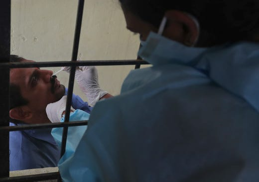 A health worker takes a nasal swab sample at a COVID-19 testing center in Hyderabad, India, Tuesday, Oct. 27, 2020. India reports 36,470 new coronavirus cases, the lowest in more than three months in a continuing downward trend. However, the overall tally neared 8 million, the second in the world behind the U.S. with over 8.7 million positive cases.