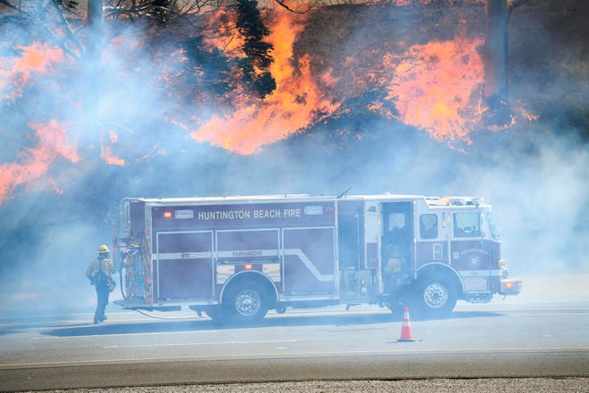 Huntington Beach Fire Department Firefighters monitor the Silverado Fire in Irvine, Calif. on Oct. 26, 2020. The Silverado Fire forced the evacuation of 60,000 Irvine residents. Powerful winds caused the brush fire to grow to over 2,000 acres and grounded aircraft from deploying critical water drops.
