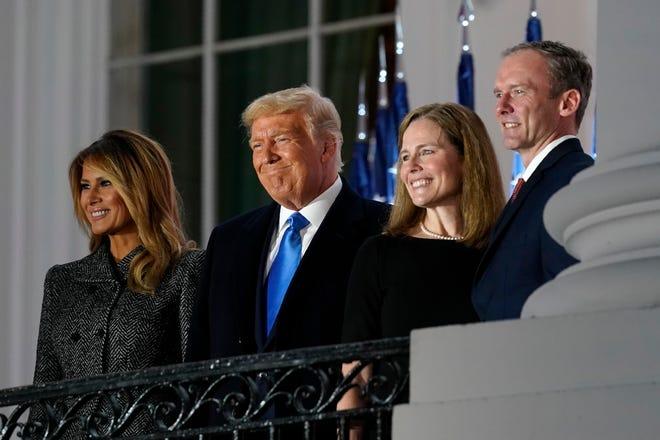 De gauche à droite, la première dame Melania Trump, le président Donald Trump, Amy Coney Barrett et Jesse Barrett, se tiennent sur le balcon de la chambre bleue après que le juge de la Cour suprême Clarence Thomas a prononcé le serment constitutionnel sur la pelouse sud de la Maison Blanche à Washington.