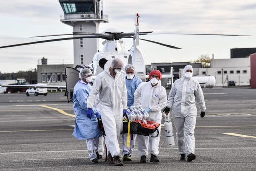 Medical staff carry medical equipment to a waiting medical flight at the Bron airport near Lyon, southeastern France, on October 27, 2020, to be evacuated on another hospital, amid the outbreak of the Covid-19 caused by the new Coronavirus.