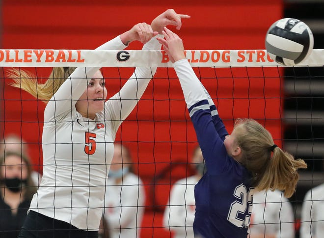 Green's Liberty Torres, facing, puts the ball over the net against Hudson's Melissa Hansen during the first set of a volleyball match at Green High School, Tuesday, Oct. 27, 2020, in Green, Ohio. [Jeff Lange/Beacon Journal]