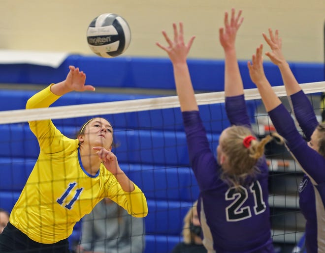 Coventry's Brooke Mirka, facing, spikes the ball past Triway's Jaymes Gilbert during the second set of a Division II district volleyball match, Wednesday, Oct. 28, 2020, in Coventry, Ohio. [Jeff Lange/Beacon Journal]