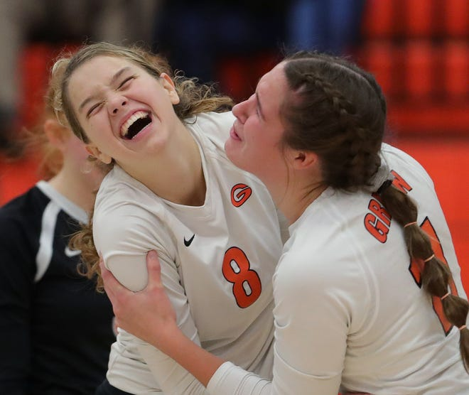 Green's Natalie Eckard, facing, celebrates with Taylor Peterson as they lead during the fifth set of a volleyball match against Hudson at Green High School, Tuesday, Oct. 27, 2020, in Green, Ohio. [Jeff Lange/Beacon Journal]