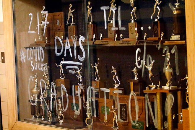 A sign written on the trophy case in the hallway outside the gym expresses how seniors at Black River High School feel about COVID-19 as the school's volleyball team plays Brookside High School in a volleyball match on Wednesday, Oct. 28 at Black River High School.