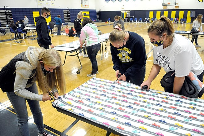 Hillsdale FFA members and high school students Lacey Fickes and Cassian Filbrun work on one of the tie blankets the chapter was making as part of the service activities during the FFA National Convention & Expo, while officer Megan Schwendeman checks on their progress Tuesday. The convention was held virtually due to the pandemic, but Hillsdale FFA made its own in-school convention, full of activities and speakers, in addition to watching the national sessions.