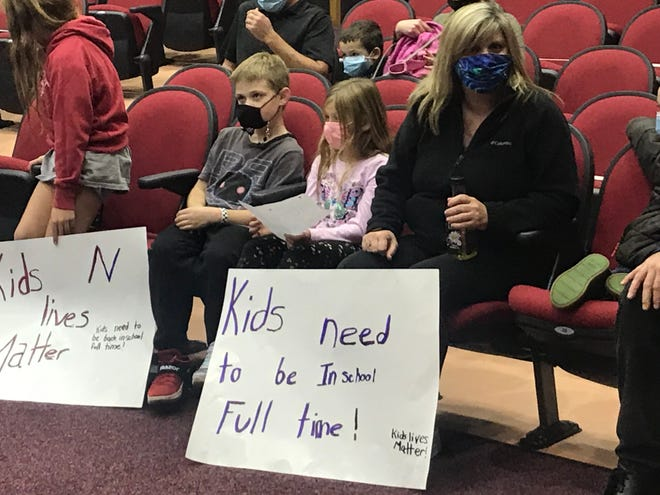 Jennifer Brown, right, and her children display signs urging a full return to classrooms choice at Tuesday night's Neshaminy School Board meeting. The board voted unanimously to delay such an option until at least Nov. 30.