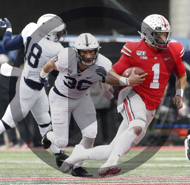 In this file photo, Ohio State Buckeyes quarterback Justin Fields (1) runs upfield for a first down ahead of Penn State Nittany Lions linebacker Jan Johnson (36) during the first quarter of the NCAA football game at Ohio Stadium in Columbus on Saturday, Nov. 23, 2019.