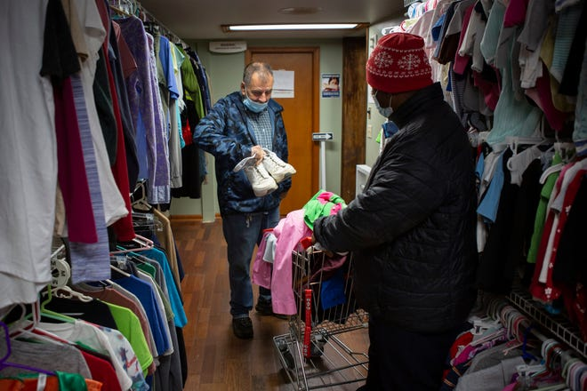 James Cooper, 61, of Delaware, shows Craig Sloan, 61, of the North Side of Columbus, a pair of shoes as they shop at the Common Ground Free Store in Delaware on Tuesday.