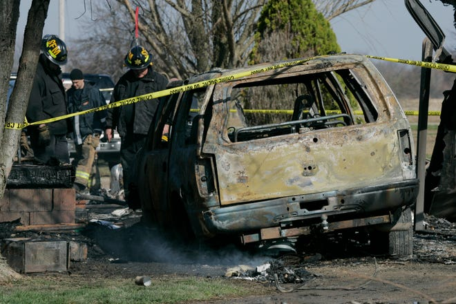 Firefighters sift through debris near the burned shell of the Romans family's 2001 Ford Expedition in the early morning hours after the April 6, 2008, fatal fire at the family's Lilly Chapel-Opossum Run Road in rural Madison County. The fire killed Billi, Ami and Caleb Romans.